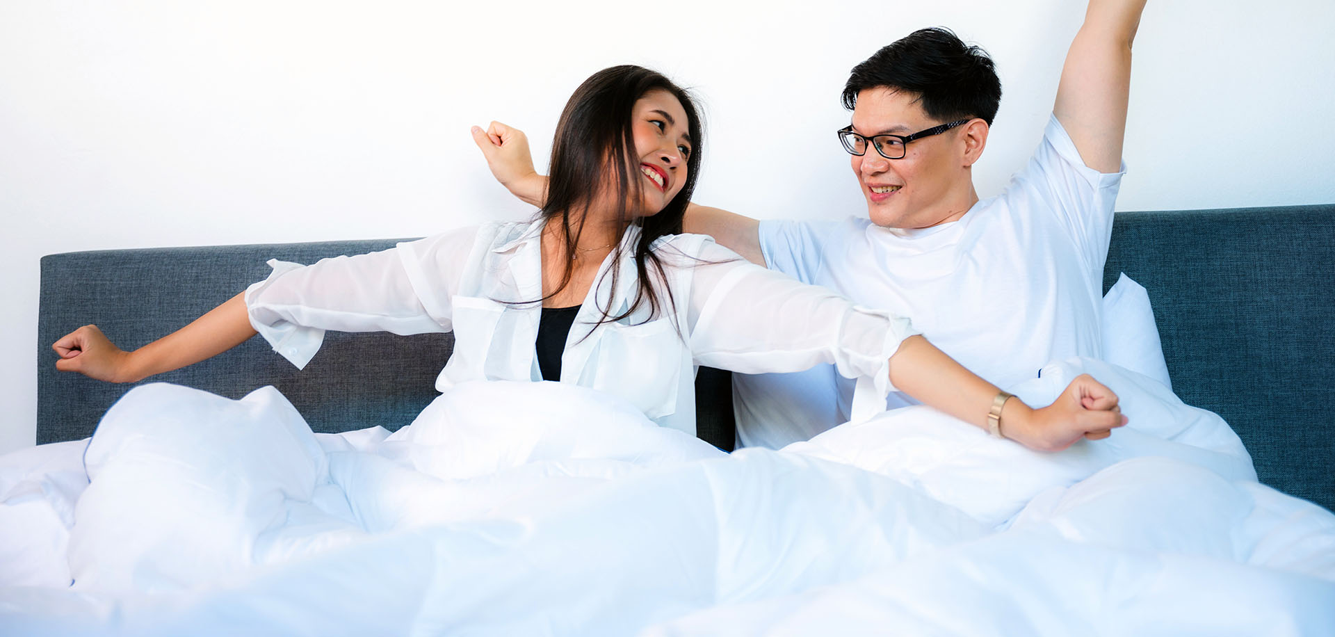 happy young couple wake up in bed and smiling raise arms in the morning, asian lovers on white bed